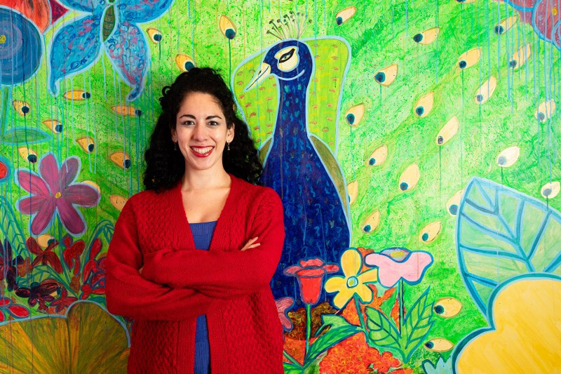 Photo of Christine Sloan Stoddard with her peacock mural by Shawn Inglima.