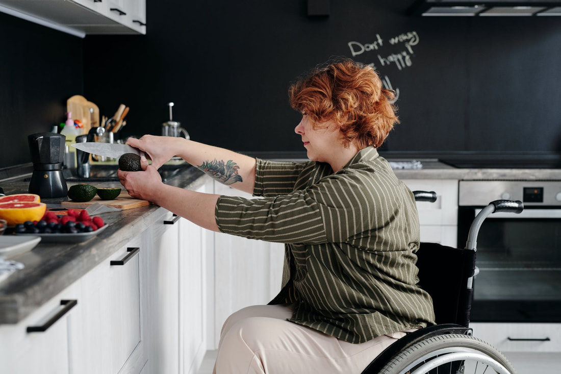 Femme-presenting person in a wheelchair cutting an avocado. In the background, a message in chalk reads